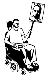 Man sitting in an electric wheelchair holding a placard with a picture of Kader that says